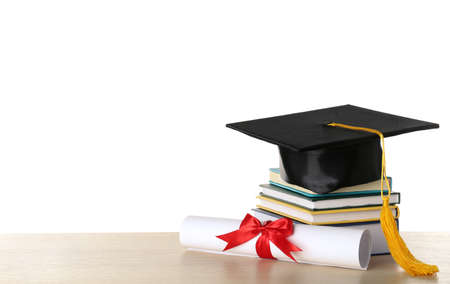 Graduation hat with books and diploma on table against white background