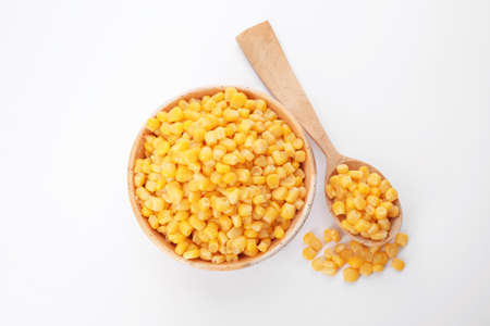 Bowl and spoon with corn kernels on white background, top view