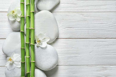Flat lay composition with green bamboo stems on wooden background. Space for text