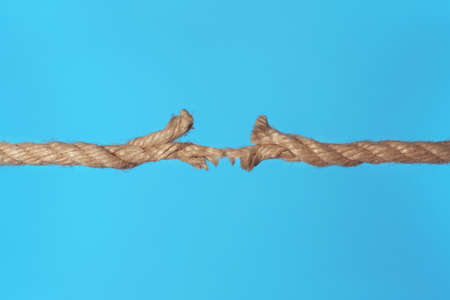 Stretched frayed rope breaking on color background