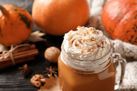 Mason jar with tasty pumpkin spice latte on table, closeup