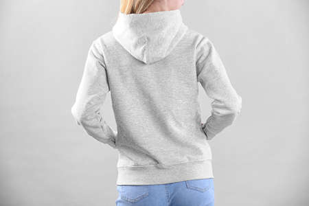 Woman in hoodie sweater on light background. Space for design Imagens