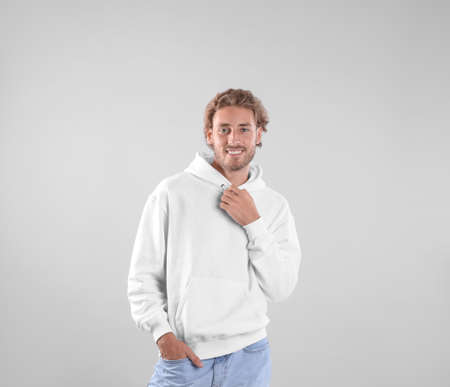 Portrait of man in hoodie sweater on light background. Space for design Foto de archivo