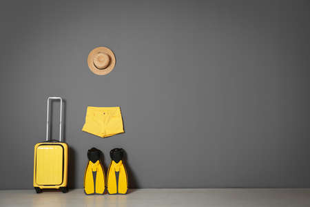 Suitcase with hat and swim fins near gray wall. Space for text