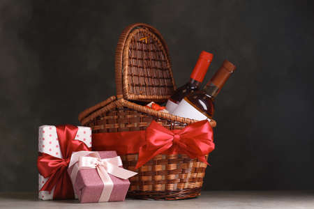 Festive basket with bottles of wine and gifts on table against dark background