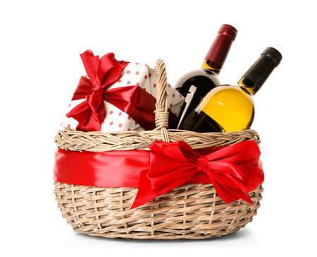 Festive basket with bottles of wine and gift on white background Imagens