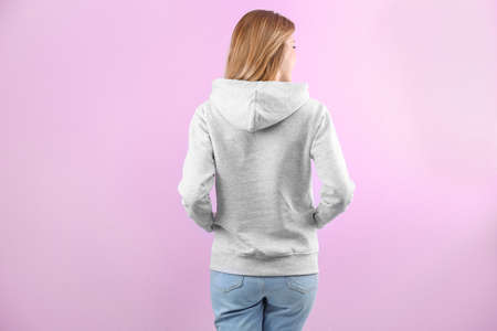 Woman in hoodie sweater on color background. Space for design Imagens