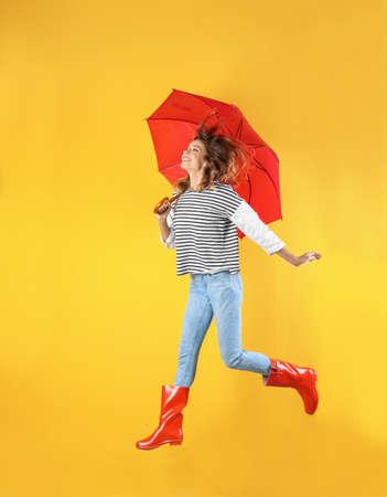 Mujer con sombrilla roja cerca de la pared de color Foto de archivo