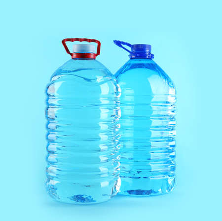 Large plastic bottles with pure water on color background
