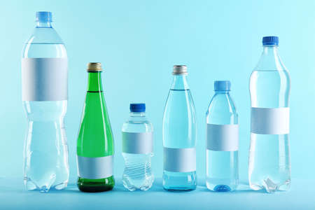 Different bottles of pure water with blank tags on color background Stock Photo