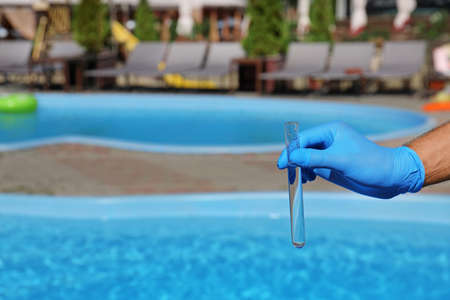 Man holding test tube with water against swimming pool on sunny day. Space for text Reklamní fotografie