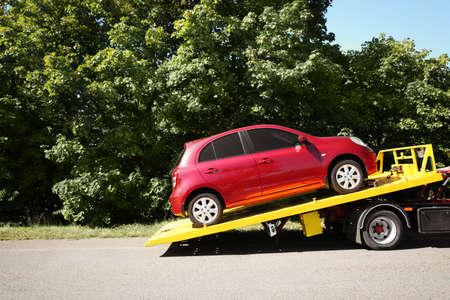 Carro attrezzi con automobile rotta sulla strada di campagna. Spazio per il testo