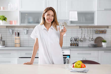 Young woman holding glass with clean water in kitchen
