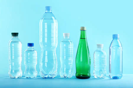Set of different plastic bottles with pure water on color background