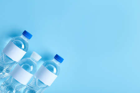 Bottles of water on color background, top view. Space for text
