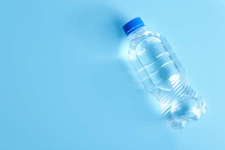 Bottle of water on color background, top view. Space for text