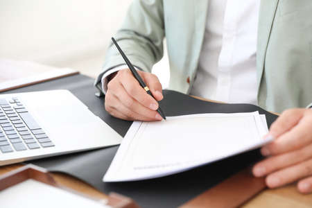 Male notary signing document at table in office, closeup