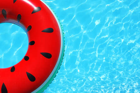 Inflatable ring floating in swimming pool on sunny day, top view with space for text Stock Photo