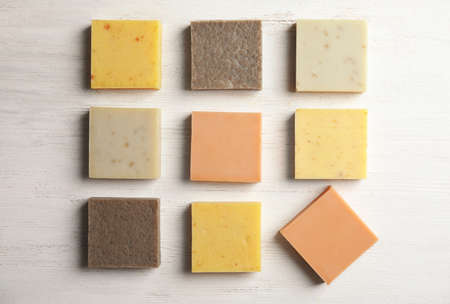 Hand made soap bars on white wooden background, top view