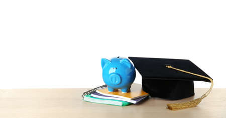 Graduation hat with piggy bank and notebooks on table against white background Stok Fotoğraf
