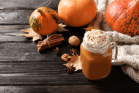 Mason jar with tasty pumpkin spice latte and space for text on wooden table Stock Photo