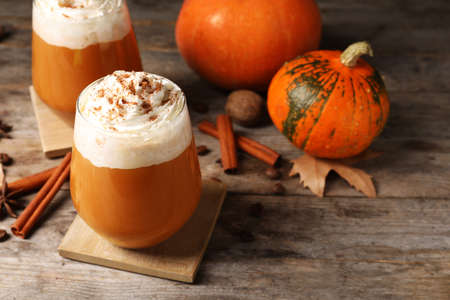Glasses with tasty pumpkin spice latte on wooden table