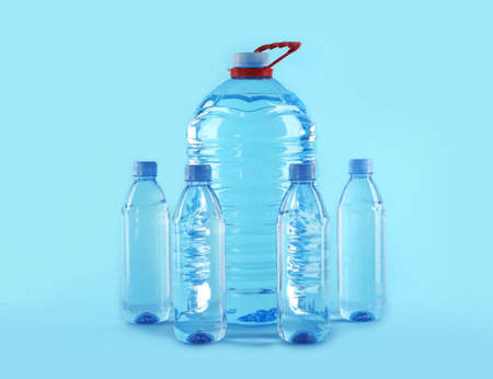 Large and small bottles with pure water on color background