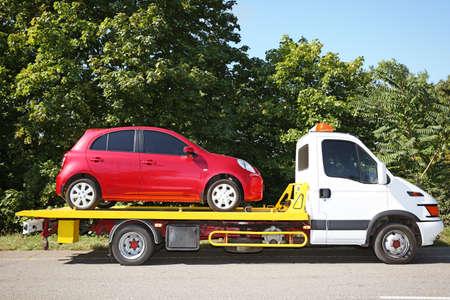 Sleepwagen met kapotte auto op landweg Stockfoto
