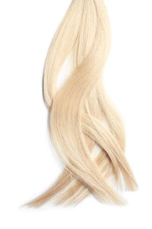 Locks of healthy blond hair on white background