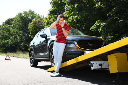 Man talking on phone near broken car and tow truck outdoors Stockfoto