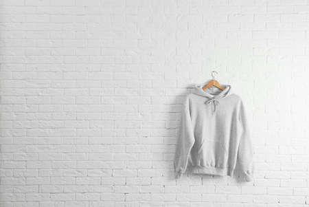 New hoodie sweater with hanger on brick wall. Mockup for design 写真素材