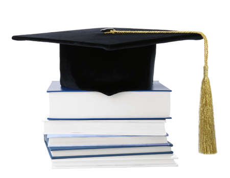 Graduation hat with gold tassel and stack of books isolated on white 写真素材
