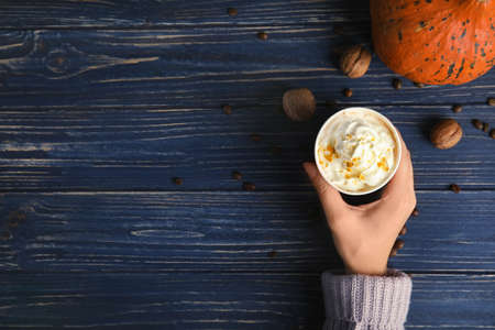 Woman holding paper cup with pumpkin spice latte on wooden background, top view. Space for text Stock Photo