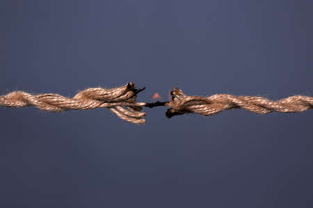 Burning rope at breaking point on dark background, closeup Stock Photo