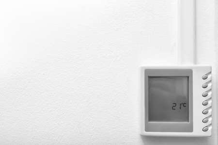 Modern thermostat and space for text on white wall. Heating system Banco de Imagens