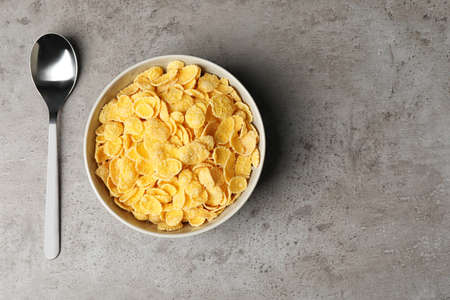 Bowl with healthy cornflakes and spoon on table, top view. Space for text Фото со стока