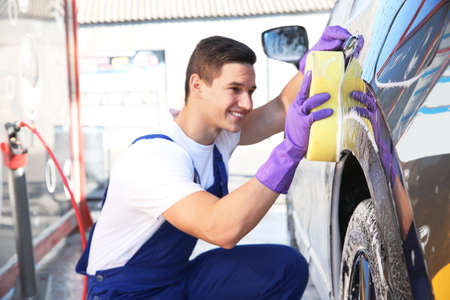 Worker cleaning automobile with sponge at car wash 写真素材