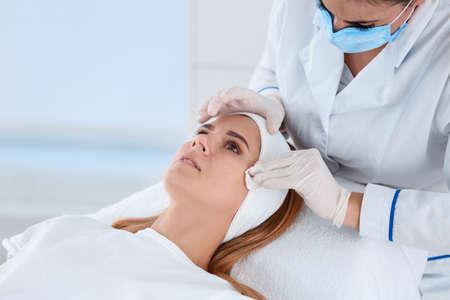 Mujer sometida a procedimiento de biorevitalización facial en el salón. Tratamiento cosmético
