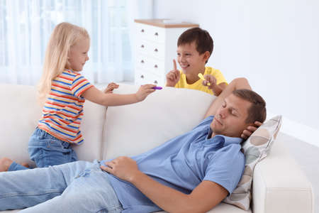 Mischievous children with markers near their sleeping father at home. Planning April fools day prank Stock Photo