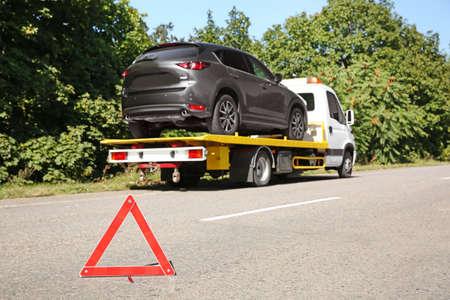 Not-Aus-Schild mit gebrochenem Auto und Abschleppwagen auf Hintergrund