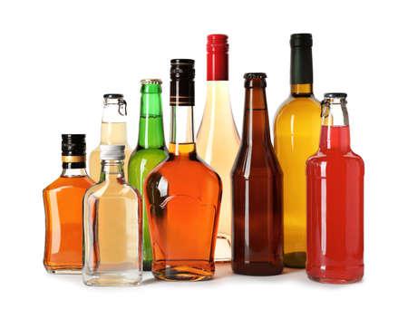 Botellas con diferentes bebidas alcohólicas sobre fondo blanco. Foto de archivo