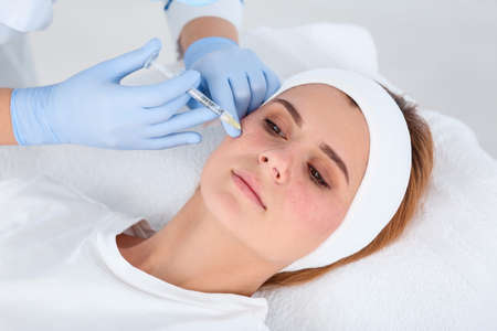 Woman undergoing face biorevitalization procedure in salon. Cosmetic treatment Stok Fotoğraf