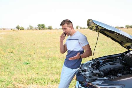 Man talking on phone near broken car outdoors. Space for text Reklamní fotografie