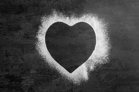 Heart-shaped frame made of flour on gray background, top view