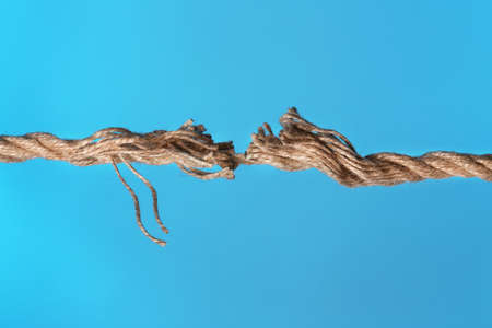 Frayed rope breaking on color background, closeup Stock Photo