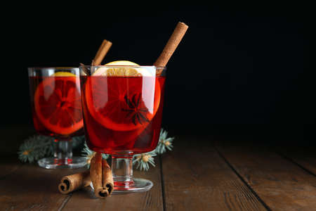 Glasses with red mulled wine on wooden table against dark background. Space for text