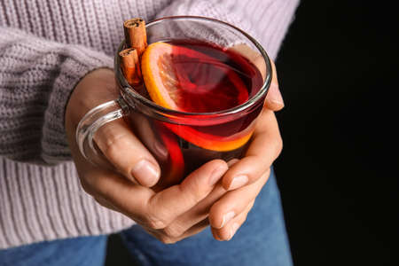 Woman holding cup with hot mulled wine against dark background, closeup
