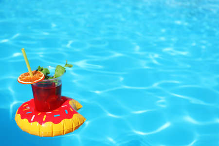 Inflatable drink holder with cocktail in swimming pool on sunny day. Space for text 스톡 콘텐츠