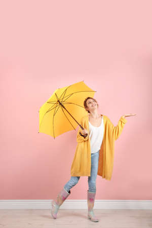 Woman with yellow umbrella near color wall Stock Photo