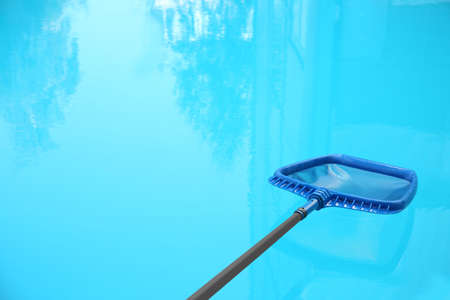 Cleaning outdoor pool with scoop net, closeup Reklamní fotografie